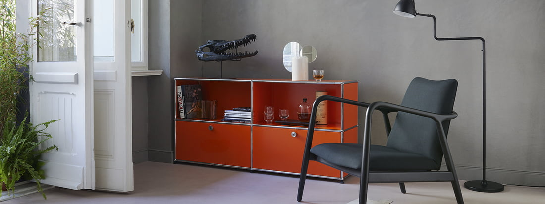 USM Haller - Herstellerserie - Wohnzimmer - Sideboard M - orange - Sessel - Stehleuchte - Bücher - Gläser - weiße Türen - Pflanzen - Ambiente
