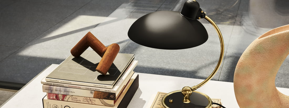 Der Schirm sowie der Fuß der KAISER idell Luxus Leuchte haben eine matt lackierte Oberfläche. Die Details bestehen aus unbehandeltem Messing und erhalten mit der Zeit eine natürliche Patina.