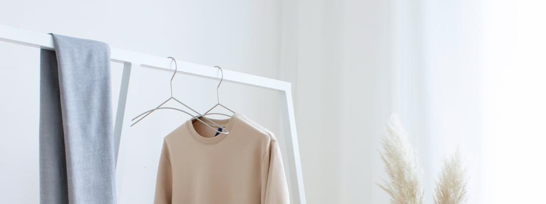 Skandinavisch schlicht wirkt die Kombination von weißer Garderobe, schwarzen Metall-Kleiderbügeln und einer kleinen Holzbank. 3 Must Haves für ein gelungenes Ankleidezimmer.