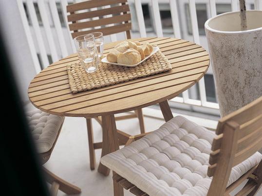 Gartenmöbel aus Holz verleihen dem Balkon einen rustikalen Look. Am Vendia Tisch mit Stühlen von Skagerak lässt es sich wunderbar unter freiem Himmel frühstücken.