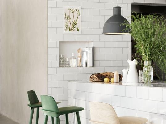 Der Nerd Barhocker aus Holz und die Unfold Pendelleuchte in grau sind moderne Accessoires für die Küche - entworfen vom skandinavischen Hersteller Muuto.