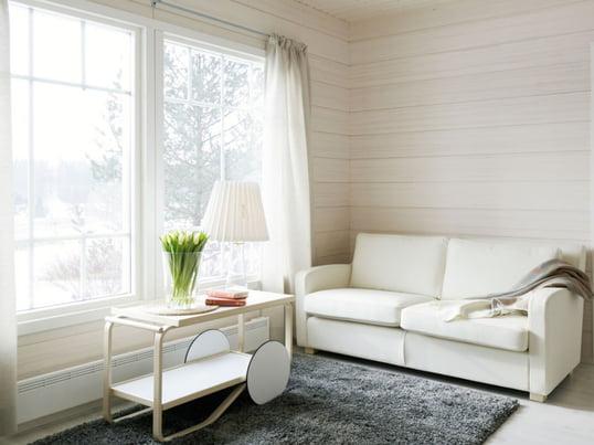 Der Servierwagen 901 von Artek ist der Hingucker in Ihrem Wohnzimmer und noch dazu ein praktischer Beistelltisch. Besonders schön wirkt er im Tageslicht, das durch das Fenster scheint.