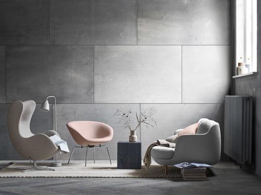Das gemütliche Lune 2-Sitzer Sofa von Fritz Hansen mit dem passenden Pot Sessel in soften Grau und Rose-Tönen. Ein modernes Wohnzimmer-Ambiente vor grauer Wand.